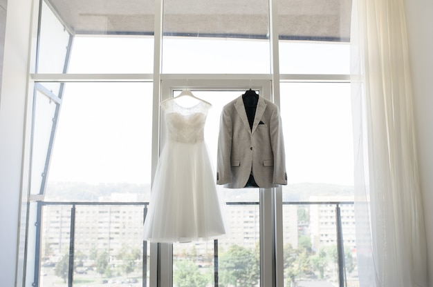 Bruidegom jas en trouwjurk op een groot raam.