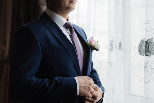 Bruidegom knoopt zijn jasje dicht bruidegom in een jasje trouwdag