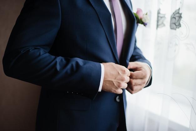 Bruidegom knoopt zijn jasje dicht man in jasje trouwdag blauw jasje