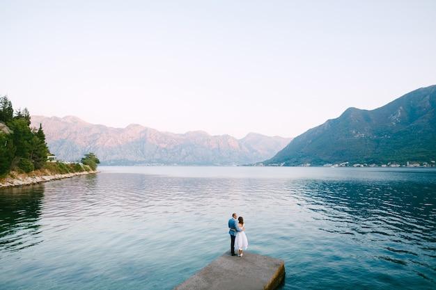 Bruidegom knuffels bruid staande op de pier