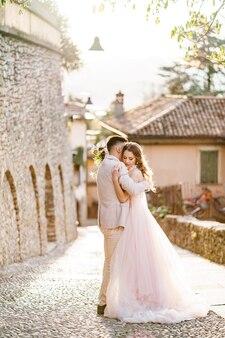 Bruidegom knuffelt bruid in een mooie jurk met een boeket bloemen
