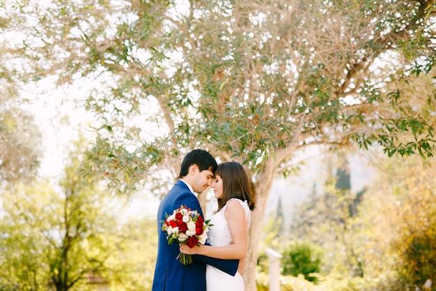 Bruidegom knuffelt bruid in een mooie witte jurk met een boeket van rode en roze rozen op een groene boom