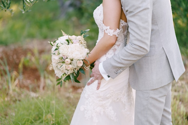 Bruidegom knuffelt bruid met een boeket bloemen in de natuur