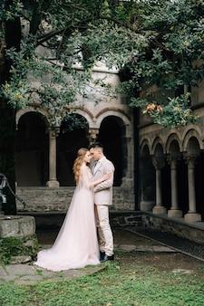Bruidegom knuffelt bruid staande in een groene tuin tegen een oude villa met kolommen