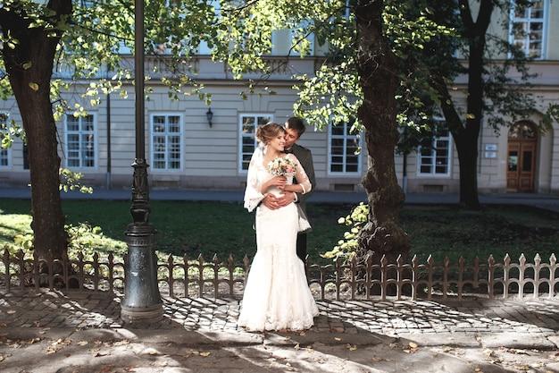 Bruidegom knuffelt bruid tegen het gebouw