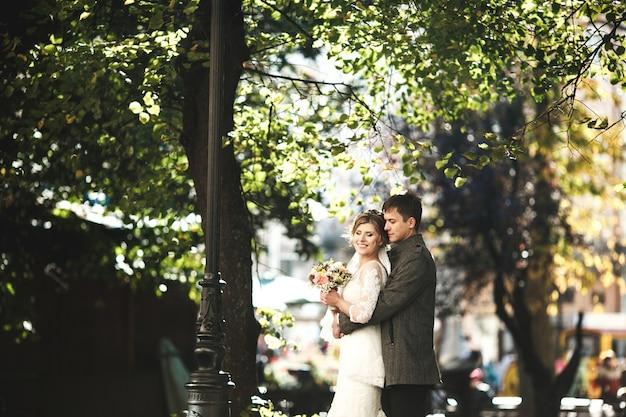 Bruidegom knuffelt bruid tegen het oude stadscentrum