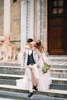 Bruidegom knuffelt en kust de bruid bij de ingang van de basiliek van santa maria