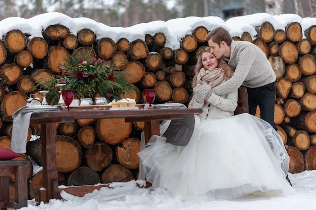 Bruidegom knuffelt teder zijn bruid vanaf de achterkant op de achtergrond van de winter bruiloft decoratie