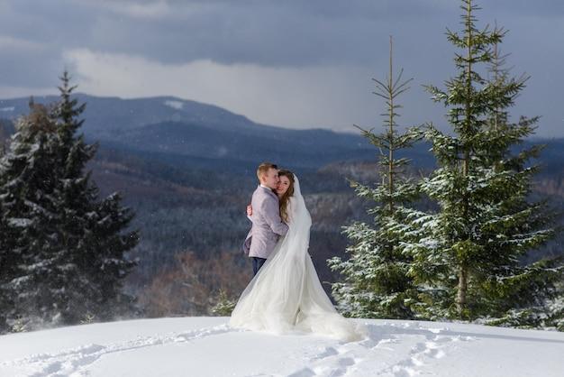Bruidegom knuffelt zijn bruid tegen de achtergrond van met sneeuw bedekte bergen. winter trouwfoto.