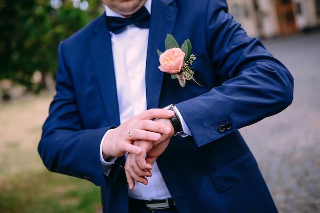 Bruidegom kostuum horloge butaan buiten kijken