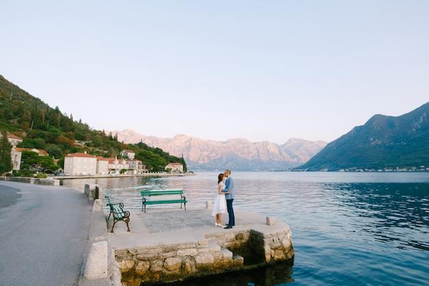 Bruidegom kust bruid in een witte jurk terwijl hij op de pier staat