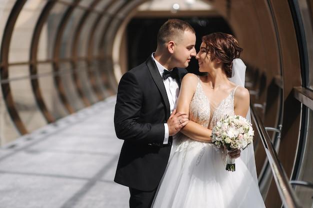 Bruidegom kust en knuffel zijn vrouw. bruid in elegante trouwjurk.