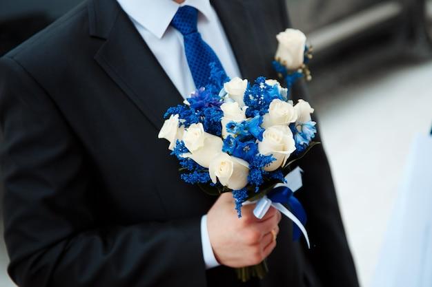 Bruidegom met een creatief winterhuwelijksboeket van verse witte rozen en delphinium