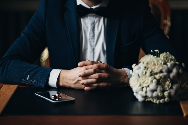 Bruidegom met trouwringen en boeket bloemen