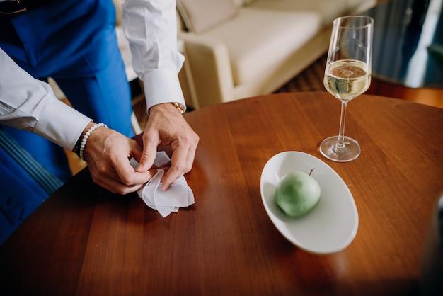 Bruidegom neemt een servet van een houten tafel