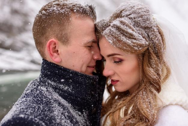 Bruidegom nestelt zich tegen zijn bruid. detailopname. het paar is bedekt met sneeuw. winter bruiloft.