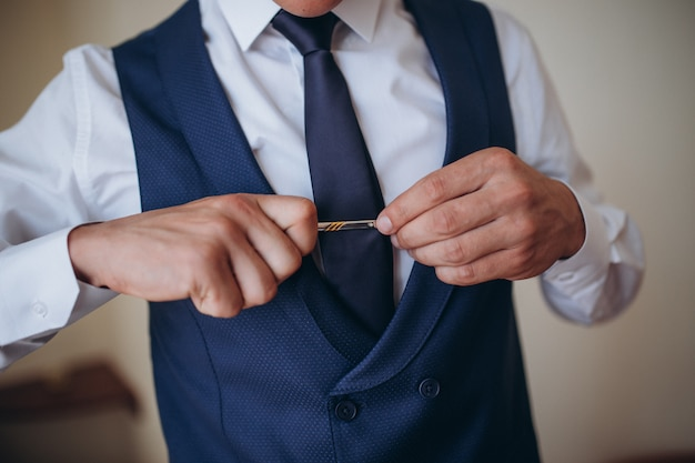 Bruidegom ochtend voorbereiding, knappe bruidegom aankleden en voorbereiden op de bruiloft, in donkerblauw pak.