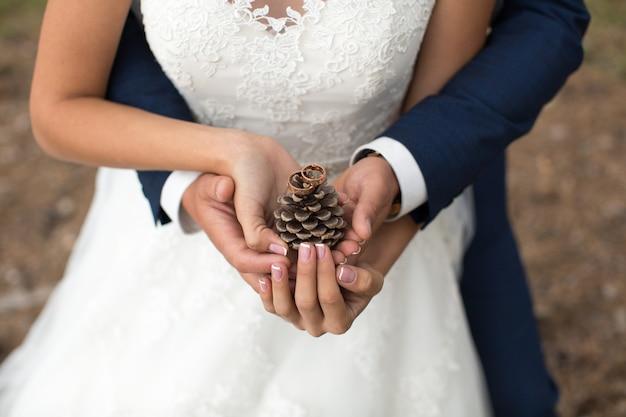 Bruidegom omhelst bruid in een dennenbos, hun handen houden een brok vast