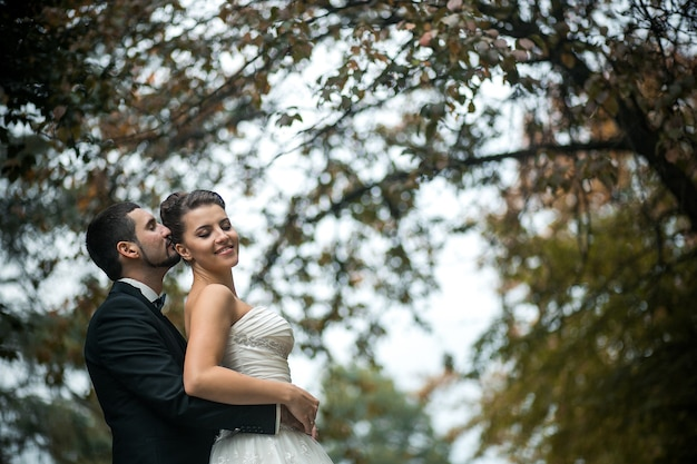 Bruidegom omhelst zachtjes de bruid met een boeket van achteren in een park