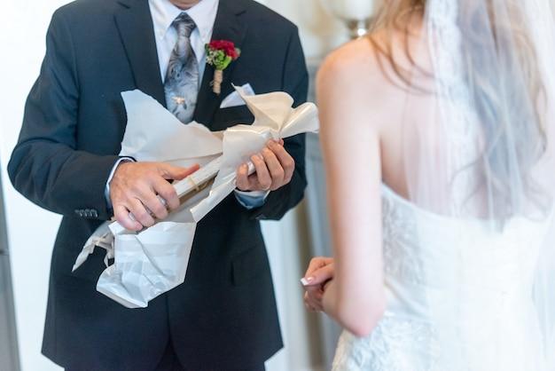 Bruidegom pakt het cadeau uit op een trouwdag