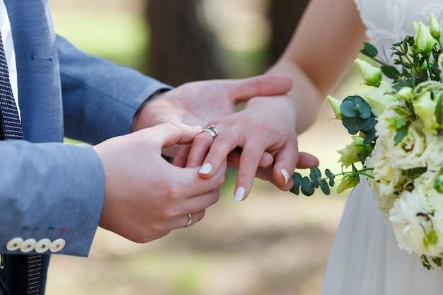 Bruidegom plaatst de ring om de vinger van de bruid