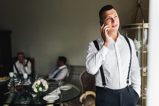 Bruidegom praat aan de telefoon voor een raam in de kamer