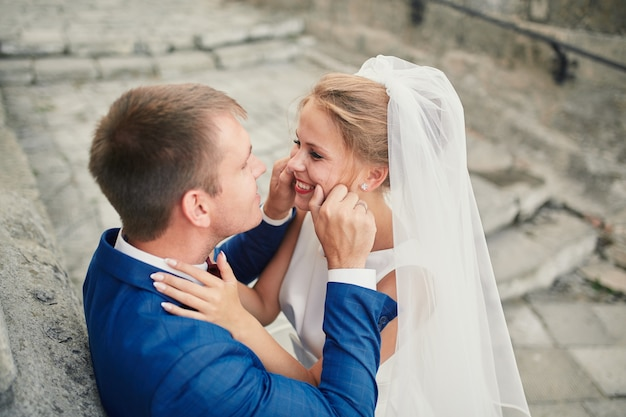 Bruidegom raakt de wangen van de bruid aan