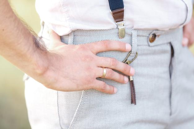 Bruidegom's hand met trouwring op een zonnige dag