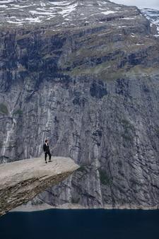 Bruidegom staat op een fragment van rots in de bergen, tegen de achtergrond van de fjord