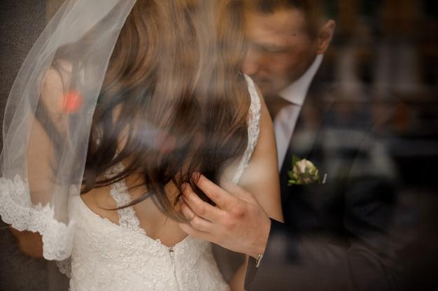 Bruidegom streelt zachtjes zijn bruid op haar rug en haar