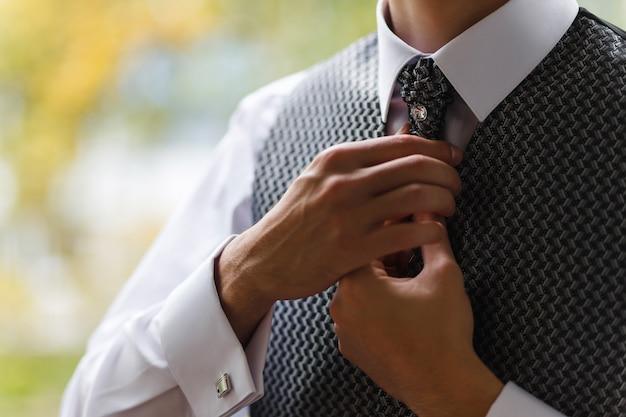 Bruidegom trekt zijn stropdas recht. de voorbereidingen van de bruidegom op de huwelijksceremonie.
