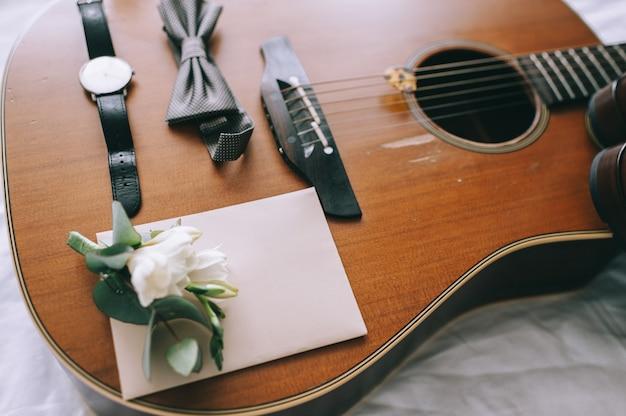 Bruidegom vlinderschoenen riemen manchetknopen horloges herenaccessoires op gitaar
