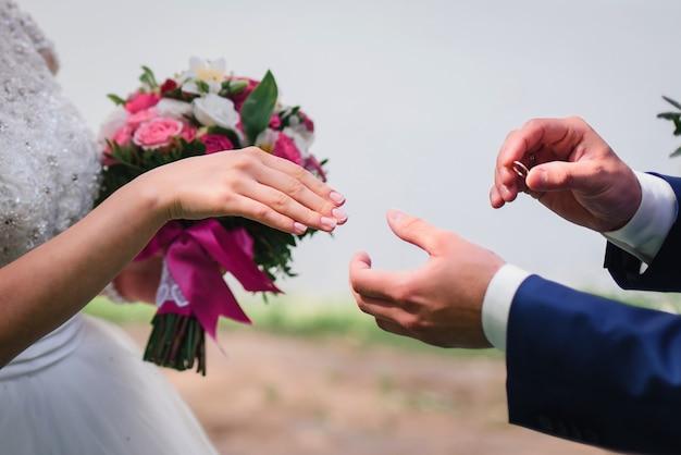 Bruidegom zet de gouden trouwring van de bruid op de hand