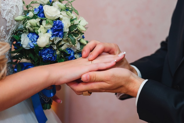 Bruidegom zet de trouwring van de bruid