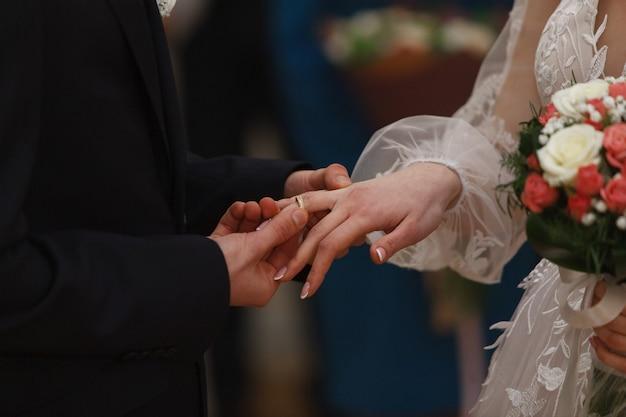 Bruidegom zet ring voor bruid.