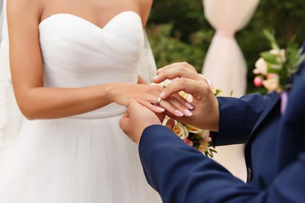 Bruidegom zet trouwring aan de bruid