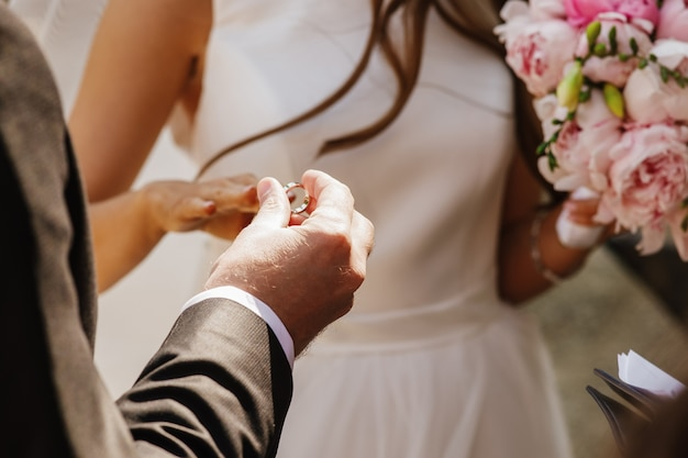 Bruidegom zet trouwring op de hand van de bruid