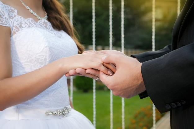 Bruidegom zet trouwring op de vinger van de bruid