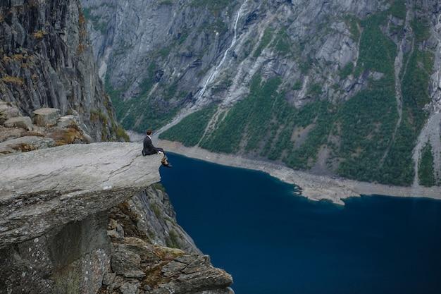 Bruidegom zittend op een fragment van rots in de bergen, tegen de achtergrond van de fjord