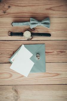 Bruidegomaccessoires voor trouwdag - horloge, vlinderdas, ringen, envelop met kopie ruimte kaart