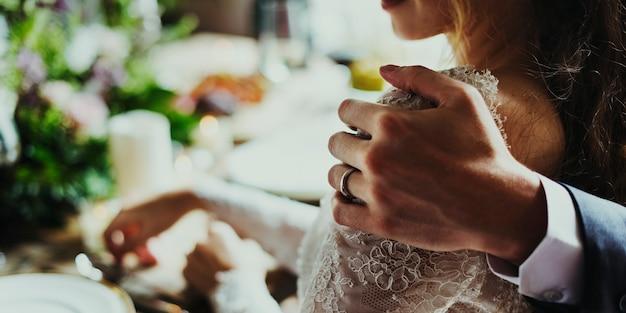 Bruidegomhand die bruid dicht op huwelijksontvangst houden