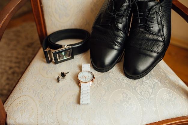 Bruidegomhorloge, schoenen en riem op een stoel