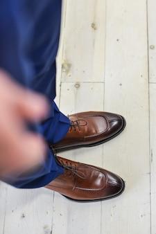 Bruidegoms lederen schoenen, bruidegom staande op de vloer