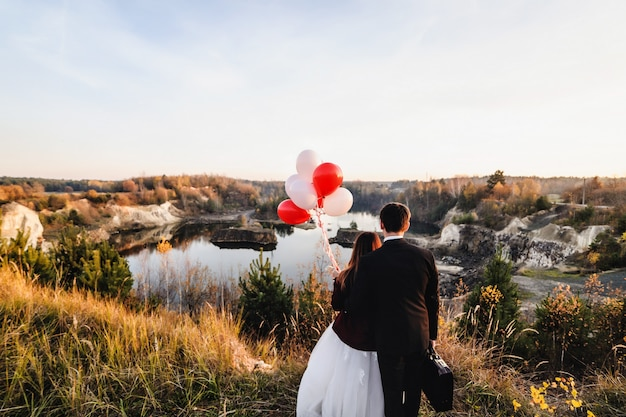 Bruidegoms zijn bij het meer en houden ballonnen. trouwkoppel.