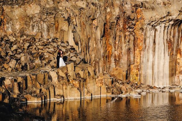 Bruiden die en bruidegom kussen kussen bij de bruine rotsen en meren.