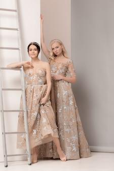 Bruiden in mooie jurk permanent binnenshuis in witte studio interieur zoals thuis.