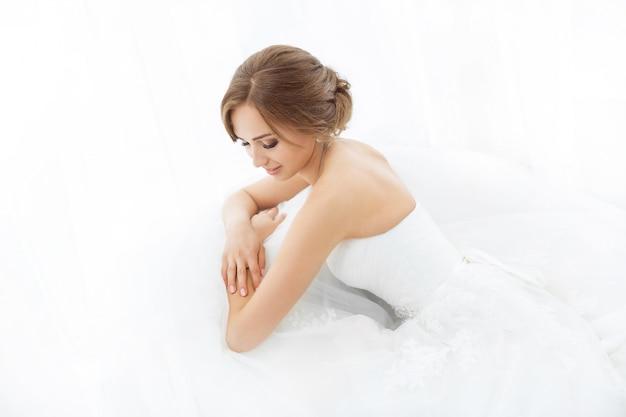Bruiden schoonheid. jonge vrouw in trouwjurk binnenshuis