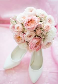 Bruids accessoires voor luxe trouwdag. huwelijk concept. trouw- en verlovingsring in de buurt van schoenen op hoge hakken, sieraden voor bruid en boeket bloemen