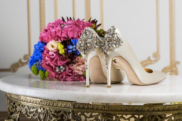 Bruids boeket en schoenen op een marmeren tafel