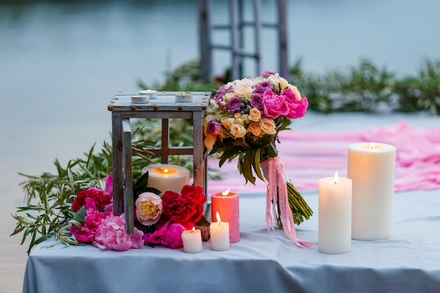 Bruids boeket onder decoratie met kaarsen en verse bloemen